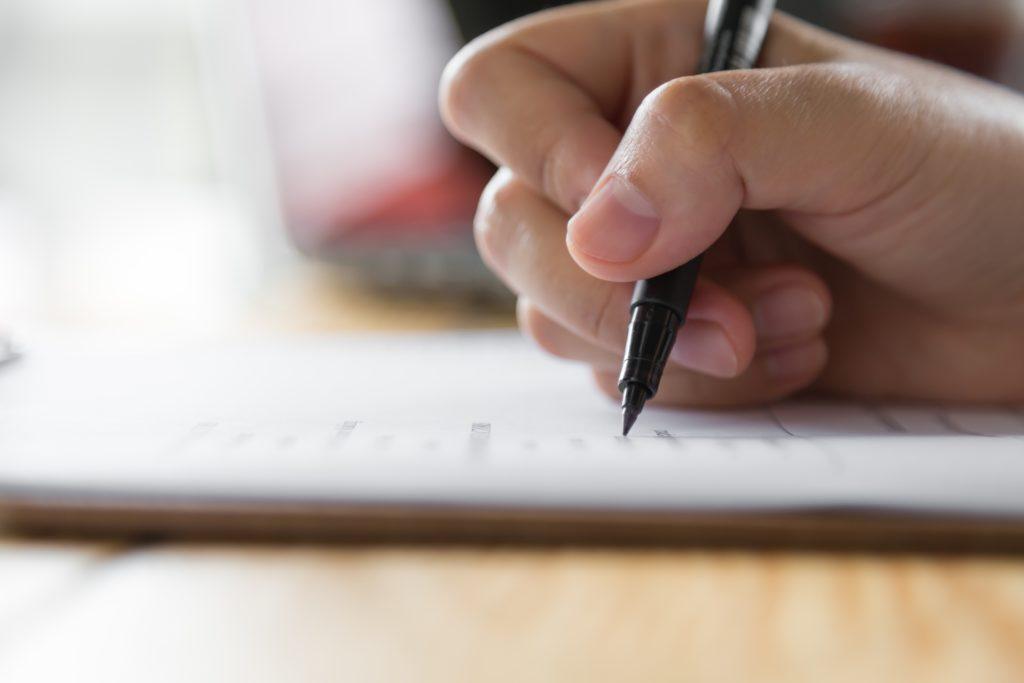 Main avec un stylo posée sur un copie d'examen de brevet.