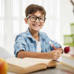 Enfant qui révise ses devoirs en souriant