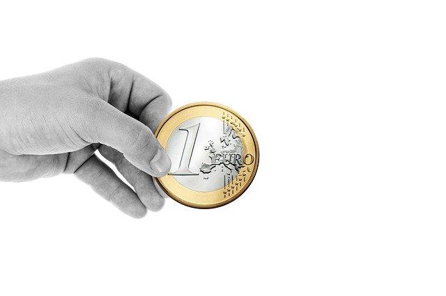 Main qui tient une pièce de 1 euro. Une pièce pour trouver la Probabilité du lancé de la pièce de monnaie